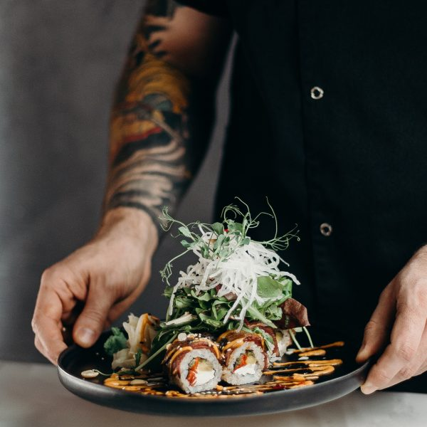 person-holding-a-plate-of-sushi-rolls-3304057.jpg